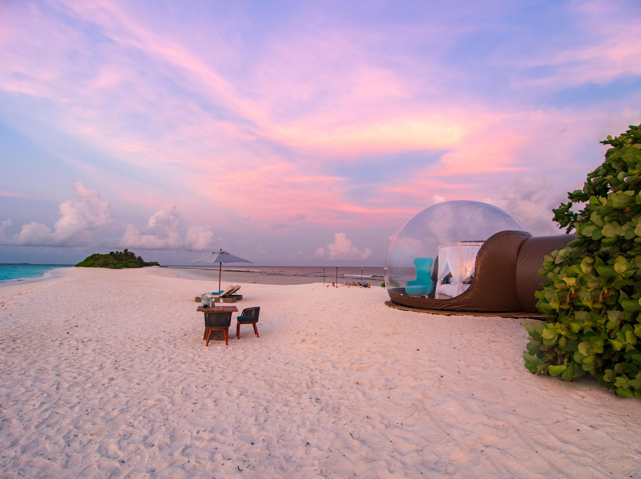 Strand des Finolhu Resorts mit Beach Bubble Tent und Tisch am Strand