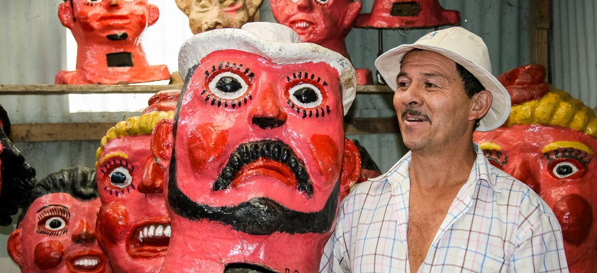 Mann mit großen Masken in Maskenmanufaktur