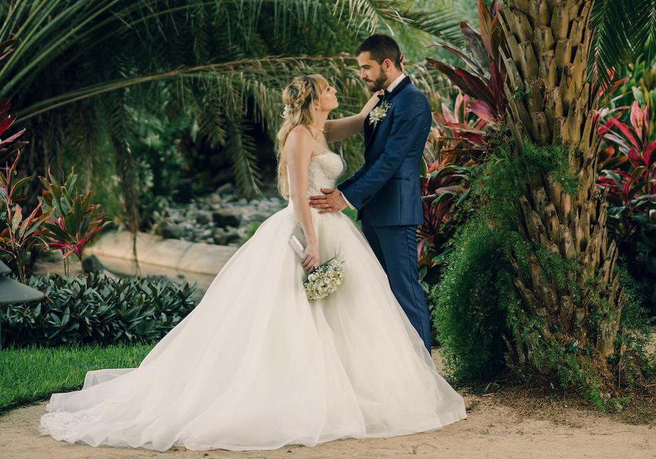 Hochzeitspaar unter Palmen blickt sich an
