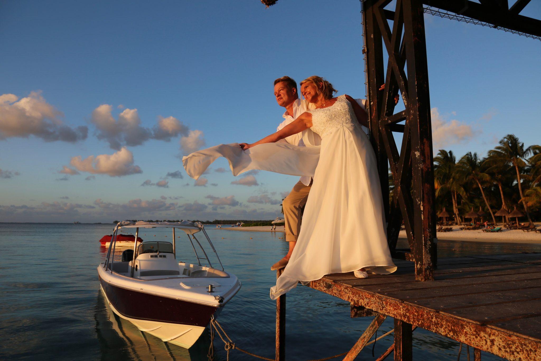 Hochzeitspaar auf einem Steg am Strand mit Boot im Hintergrund