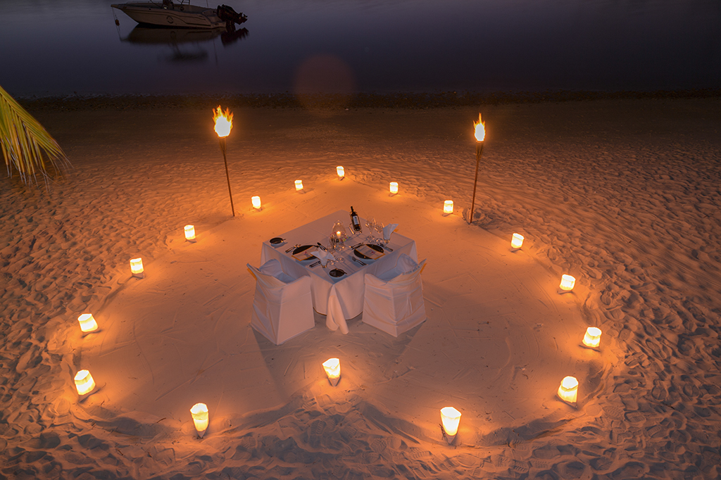Romantisch gedeckter Tisch mit Kerzen in Herzform am Strand