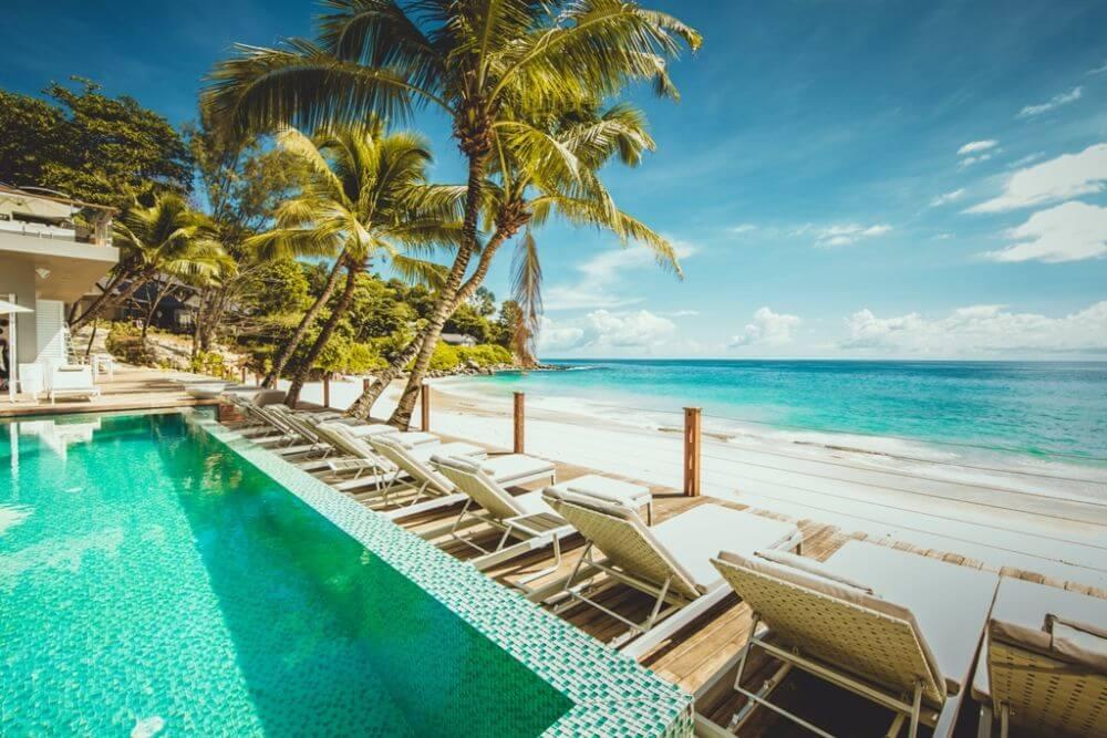 Pool und Sonnenliegen am Meer