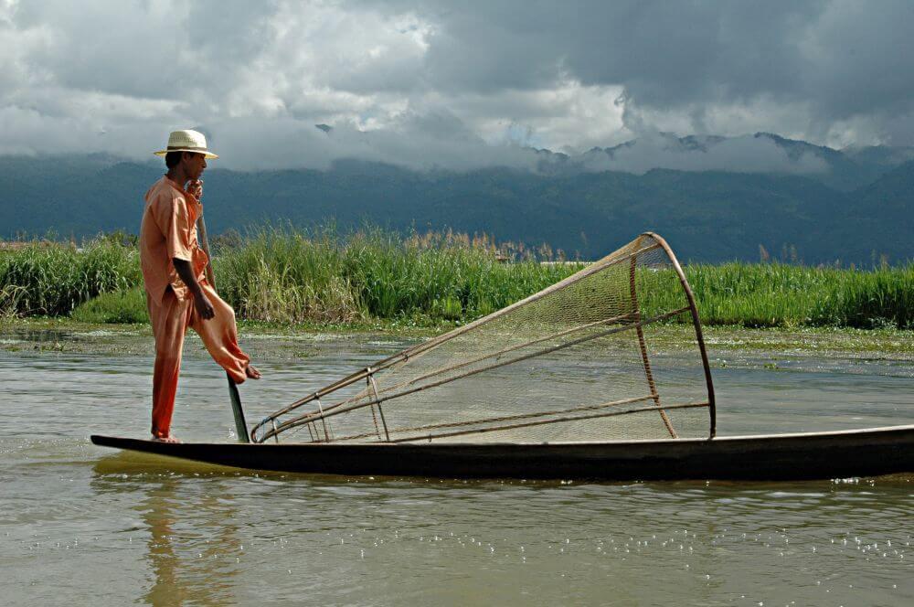 Fischer auf seinem Boot mit Netz