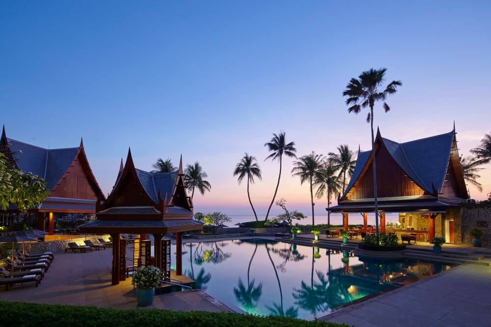 Pool im Abendlicht mit Palmen und Pavillons