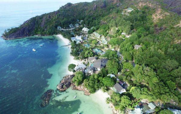 Hotel direkt am Strand am Hang mit Palmen
